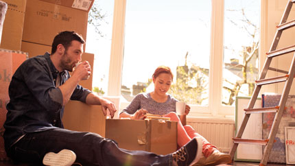 A couple who are sitting down excited in their new home among boxes of their belongings.