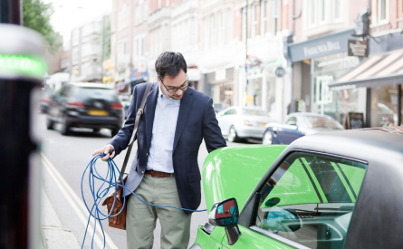 A man charging an electric car
