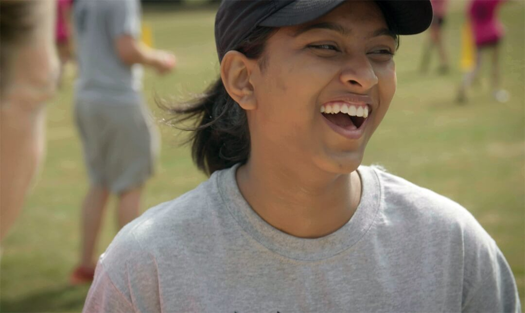 laughing girl playing cricket